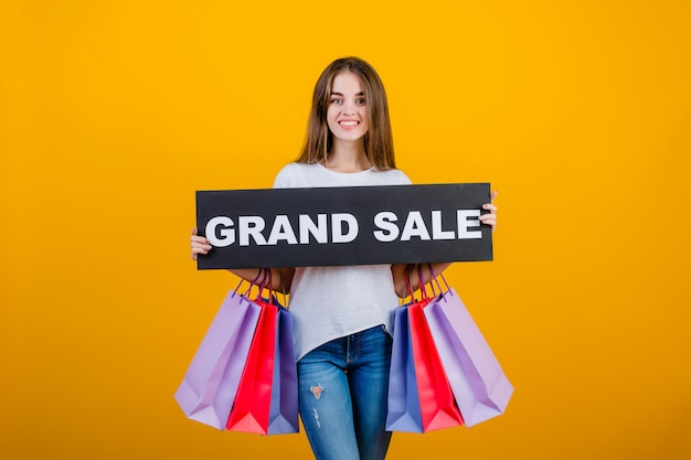 Beautiful brunette woman with colorful shopping bags and copyspace text grand sale sign banner isolated over yellow