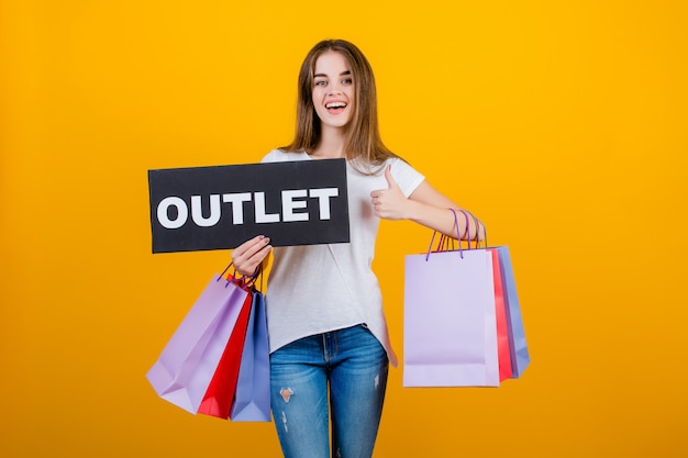 Beautiful brunette woman with colorful shopping bags and copyspace text outlet sign banner isolated over yellow