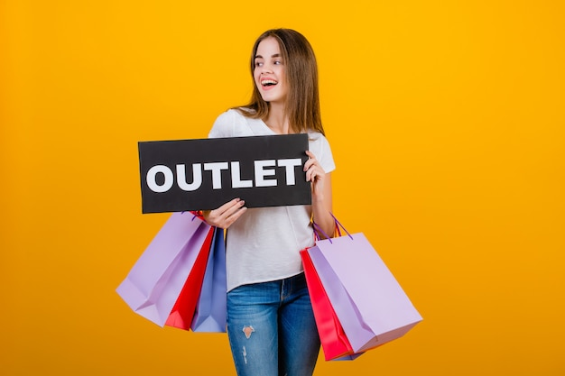 Beautiful brunette woman with colorful shopping bags and copyspace text outlet sign isolated over yellow