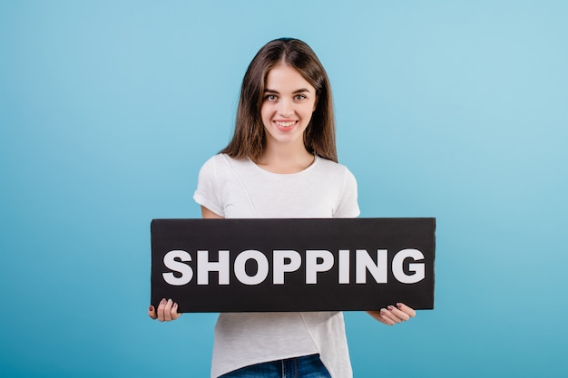 Beautiful brunette woman with copyspace text shopping sign banner isolated over blue