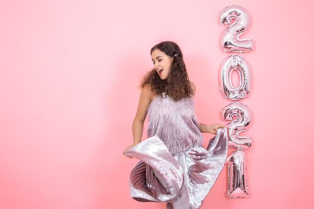 Красивая брюнетка женщина с вьющимися волосами в праздничной одежде в движении на розовой стене с серебряными шарами для новогодней концепции