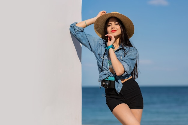 Beautiful brunette woman with figure in shorts and straw hat posing on the beach.