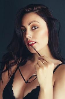 검은 바탕에 붉은 입술 근처 안경을 쓴 아름다운 갈색 머리 여자. 카메라의 모습입니다.