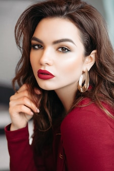 Beautiful brunette woman with golden earrings and bright lips