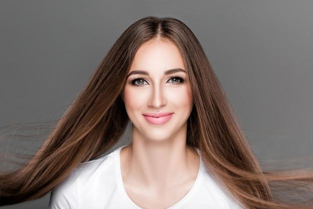 Красивая женщина брюнет с шикарными сияющими длинными волосами летания. уход за волосами