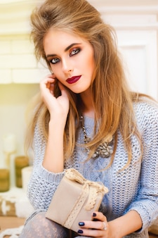 休日の美しいブルネットの女性はセーターを着てメイクアップ 無料写真