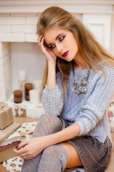 休日の美しいブルネットの女性はセーターを着てメイクアップ
