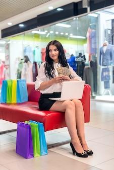 ノートパソコン、ショッピングバッグ、ドルを持つ美しいブルネットの女性