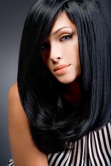 스튜디오에서 포즈를 취하 긴 검은 스트레이트 머리를 가진 아름 다운 갈색 머리 여자