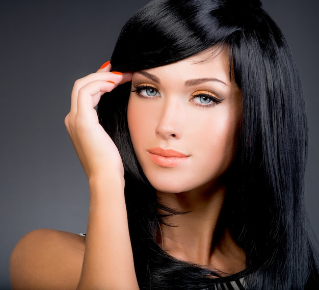 Красивая брюнетка женщина с длинными черными прямыми волосами позирует в студии