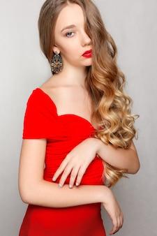 Красивая брюнетка женщина с длинными завитыми волосами в красном платье, носить серьги.