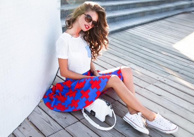Bella donna castana con capelli ondulati lunghi che si siede sulla strada