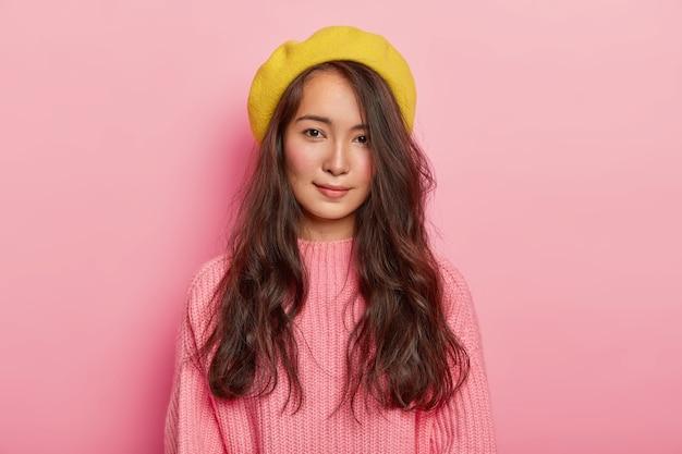 혼혈 외모를 가진 아름다운 갈색 머리 여자, 노란색 베레모와 분홍색 니트 스웨터를 입고
