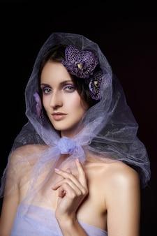 暗い背景にポーズをとって自然なメイクで美しいブルネットの女性。滑らかで繊細な顔の肌