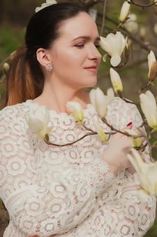 裸のメイク、レースのブラウスを着て、咲くモクレンの花の近くでポーズをとって美しいブルネットの女性