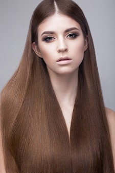 Beautiful brunette woman with a perfectly smooth hair and classic make-up