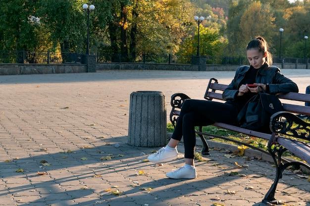 Красивая брюнетка женщина с телефоном в руке сидит в парке. отдыхает на открытом воздухе.