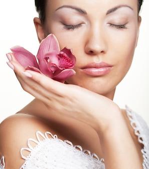 Красивая брюнетка женщина с розовой орхидеей над белым пространством, крупным планом