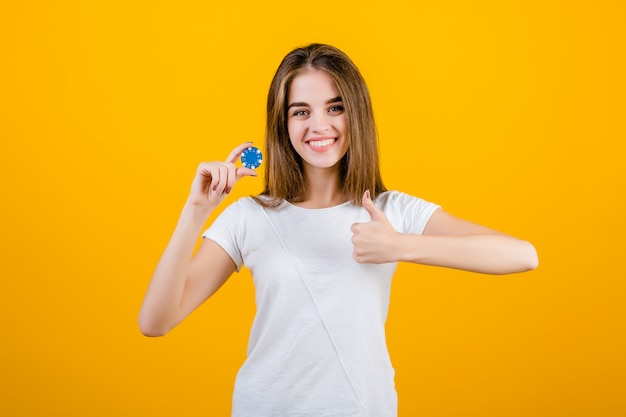 Красивая брюнетка женщина с фишкой для покера из онлайн-казино, показывая пальцы вверх изолированные над желтым