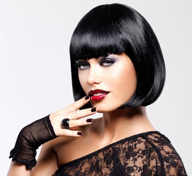 ショット黒髪型の美しいブルネットの女性。真っ赤なセクシーな唇を持つ女性モデルのクローズアップの肖像画