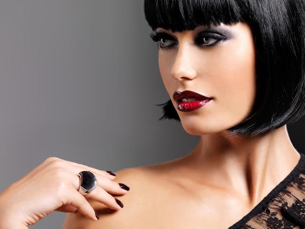 총된 검은 헤어 스타일으로 아름 다운 갈색 머리 여자입니다. 밝은 빨간색 섹시한 입술로 여성 모델의 근접 촬영 초상화