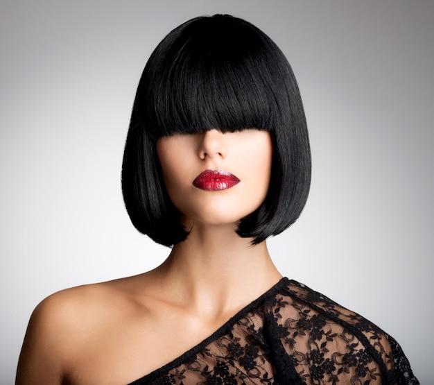 ショットの髪型とセクシーな赤い唇を持つ美しいブルネットの女性。ファッションメイクと女性モデルのクローズアップの肖像画