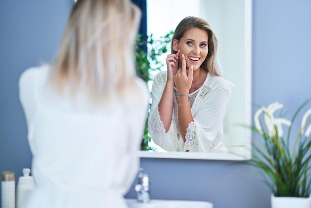 バスルームで肌の問題を持つ美しいブルネットの女性