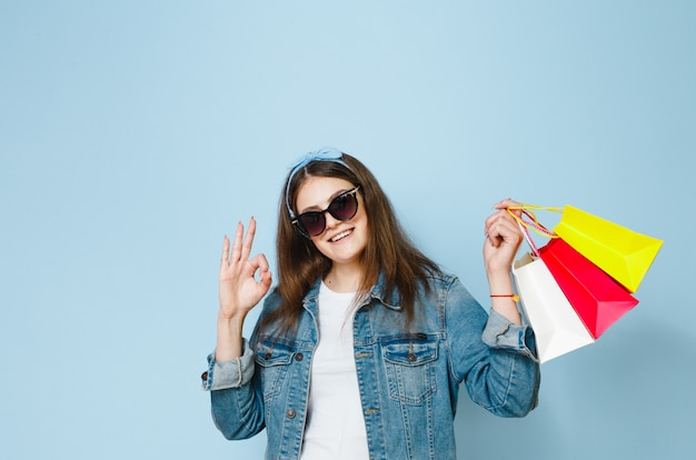 Beautiful brunette woman with sunglasses enjoys the shopping she has made on a blue background