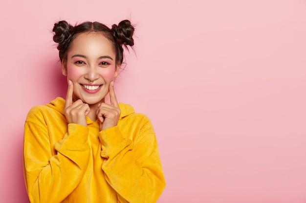 2つのパン、頬に人差し指を向け、カジュアルなコーデュオイの黄色いスウェットシャツを着た美しいブルネットの女性は、明るいピンナップメイクを着ています