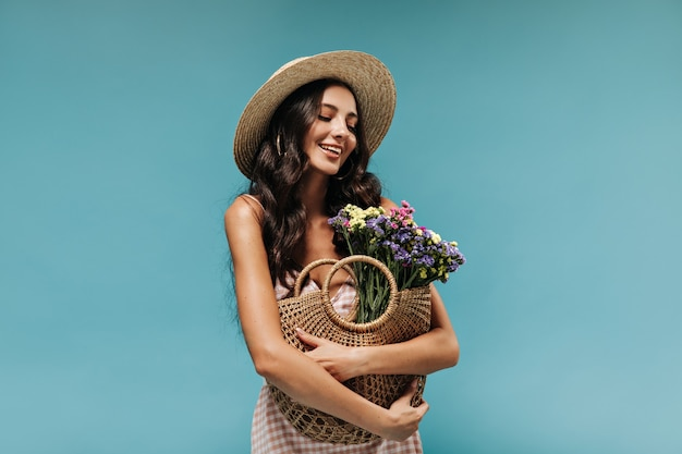 Beautiful brunette woman with wavy long hair in wide-brimmed straw hat and sundress holding bag with wildflowers on blue wall