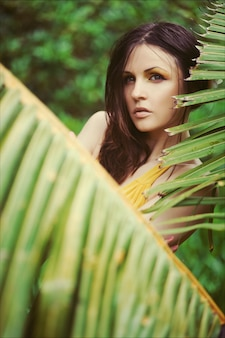Beautiful brunette woman with wet hair in yellow long dress surrounded by tropical plants