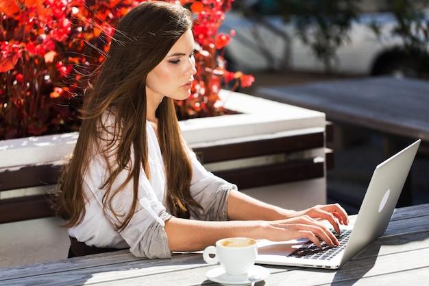아름 다운 갈색 머리 밖에 서 노트북으로 작동