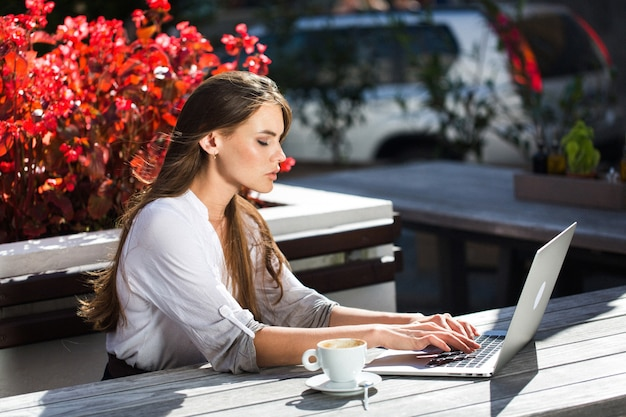 Beautiful brunette works with laptop outside