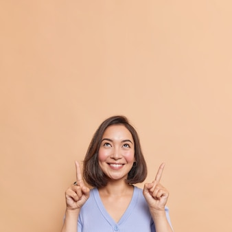 Beautiful brunette young asian woman shows discount store banner on copy space smiles gently indicates upwards poses against beige wall