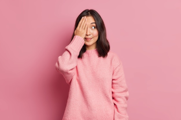Beautiful brunette young asian woman with eastern appearance covers eyes with hand hides face smiles pleasantly wears casual knitted sweater poses