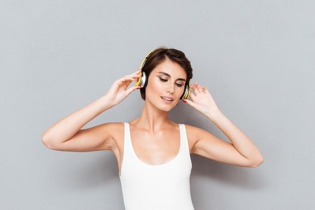 회색 배경에 고립 된 헤드폰으로 음악을 듣고 아름 다운 갈색 머리 젊은 여자