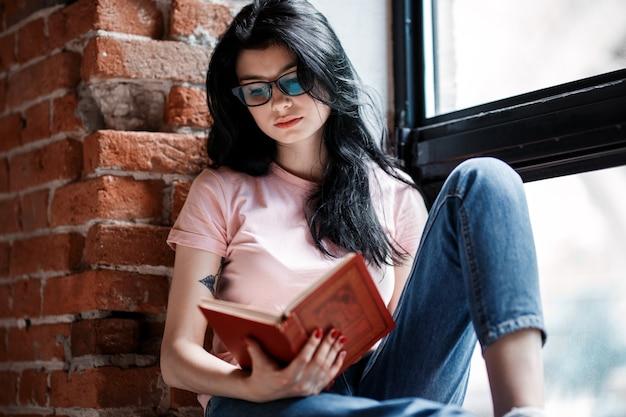 Красивая книга чтения молодой женщины брюнет у окна дома.