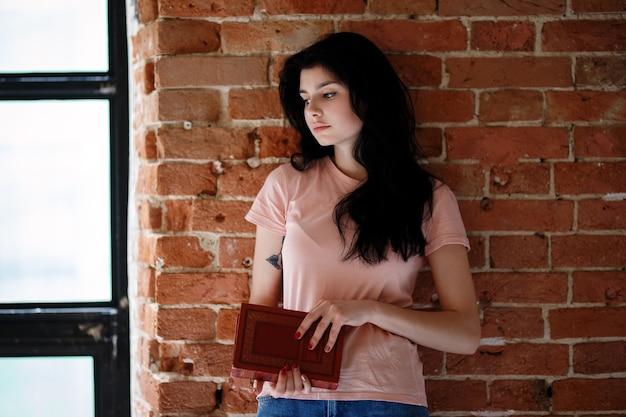 Красивая молодая женщина брюнет с книгой стоя около кирпичной стены.