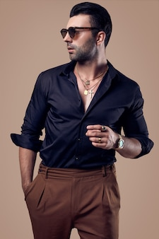 Beautiful brutal tanned hipster man in a black shirt and glasses