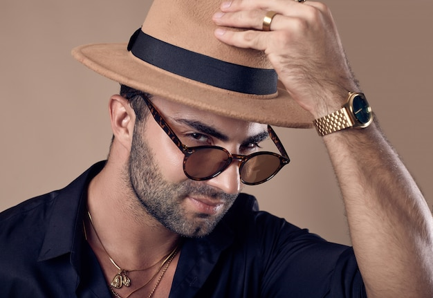 Beautiful brutal tanned hipster man in a black shirt, hat and glasses