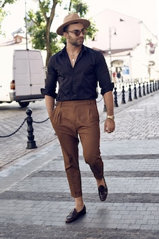 Beautiful brutal tanned muscular hipster man posing in the streets