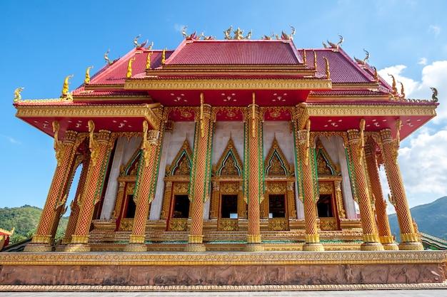 Красивый буддийский храм с позолоченными колоннами и красной орнаментированной крышей Premium Фотографии
