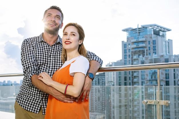 美しい建物。彼らの新しい家を見ながらバルコニーに一緒に立っている喜んでポジティブなカップル