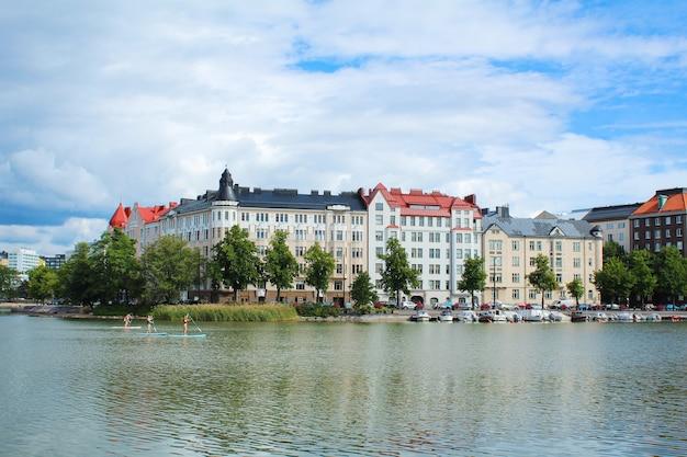 川岸の美しい建物と雲と青い空の下の緑の木々、パドルボードで航海する人々-フィンランド、ヘルシンキ、2018年8月