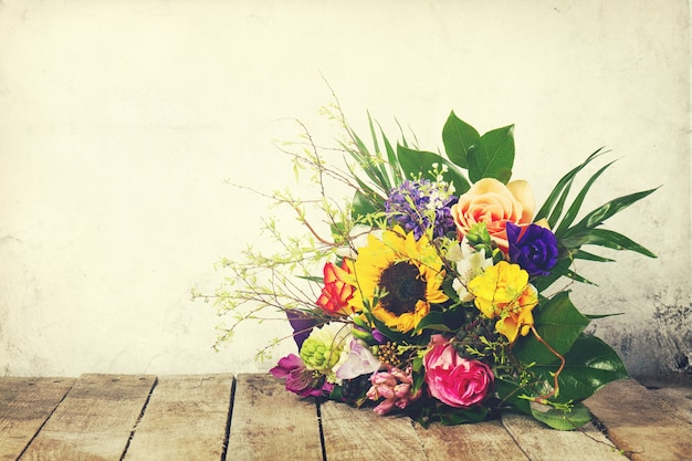 Beautiful bunch of flowers on wooden background. horizontal. vintage toning.