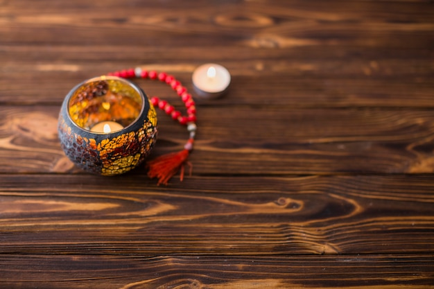 Beautiful burning candle inside the holder with red holy beads on wooden desk