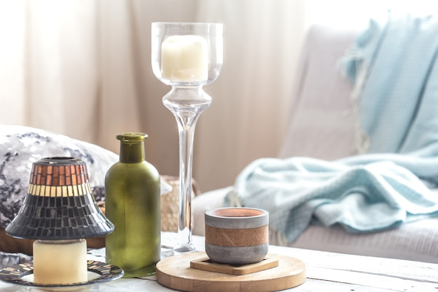 Beautiful burning candles with bottles on white table
