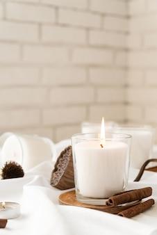 Красивые горящие свечи с корицей и сухими цветами на белой поверхности ткани
