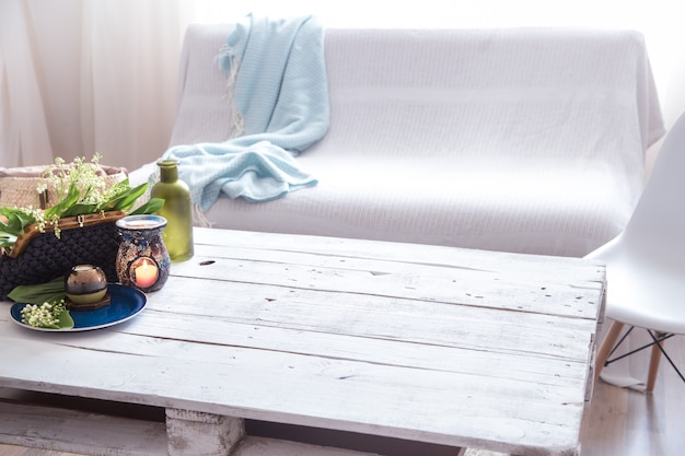 Красивые зажженные свечи с зелеными листьями в сумочке на белом столе