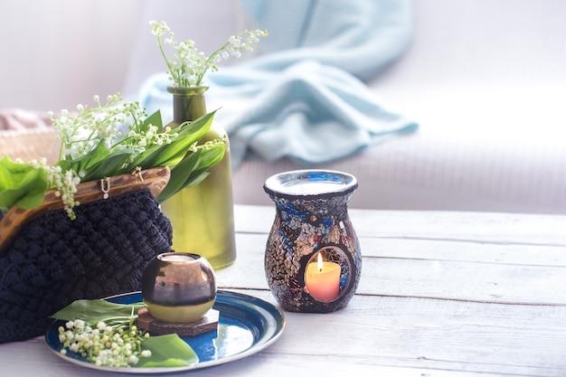 白いテーブルの上の財布に緑の葉と美しい燃えるろうそく